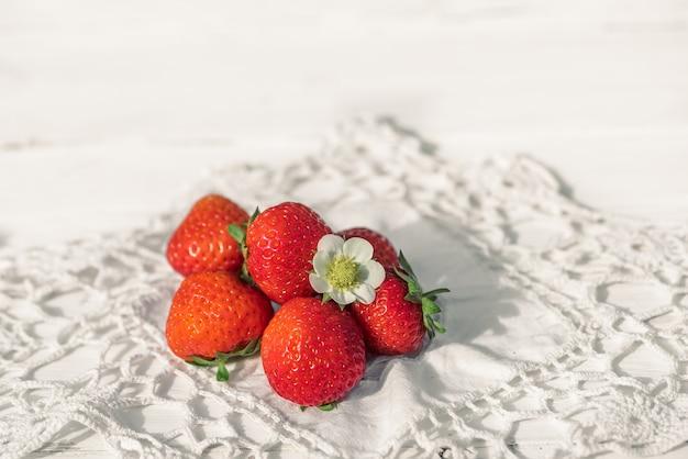 Erdbeeren auf einem weißen alten hölzernen hintergrund, gestrickte serviette