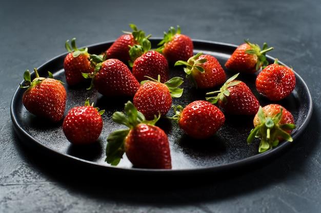 Erdbeeren auf einer schwarzen platte.