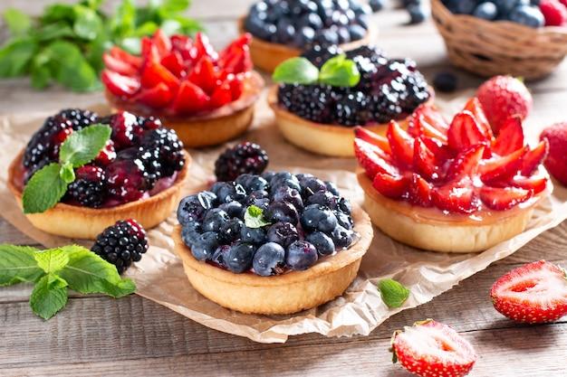 Erdbeeren, blaubeeren, brombeer-törtchen mit schokoladenganache, frische beeren und minzblätter, selektiver fokus. frische obsttorte, frischer hausgemachter obstkuchen auf einem tisch