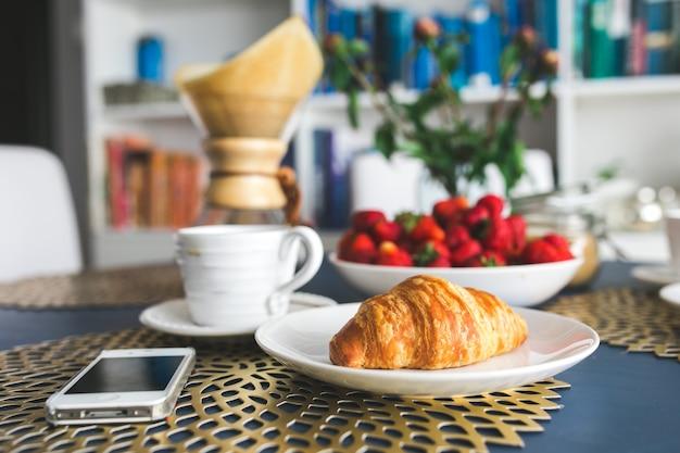 Erdbeeren, croissant, handy und eine tasse kaffee auf dem tisch
