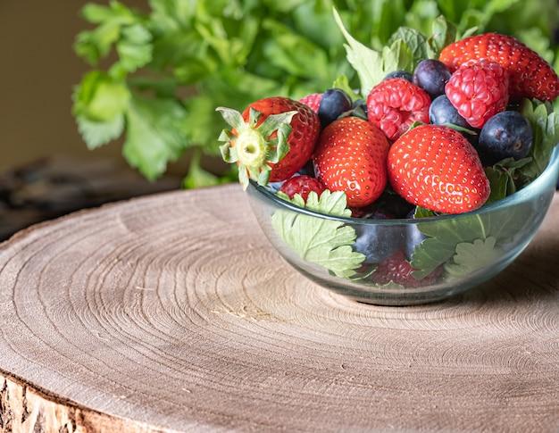 Erdbeeren, himbeeren und heidelbeeren in einer glasschale mit rustikalem hintergrund serviert served