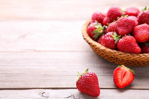 Erdbeeren im korb auf grauem holz