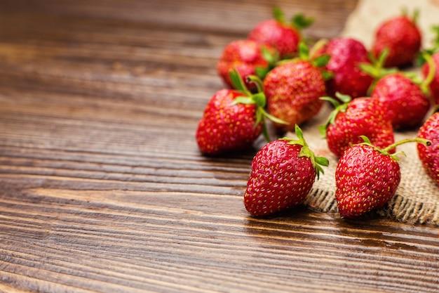 Erdbeeren im korb, erdbeerkorb, erdbeeren auf holztisch, erdbeeren auf einem braunen hintergrund, korb mit erdbeeren, erdbeeren im natürlichen hintergrund