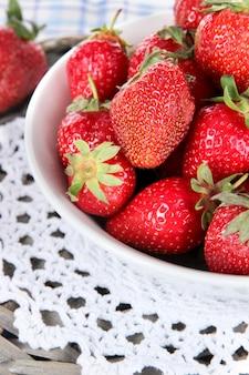 Erdbeeren im teller auf weidenständer auf serviettennahaufnahme
