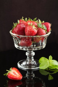 Erdbeeren in der schönen glasvase auf dem schwarzen hintergrund. lage vertikal. nahansicht.