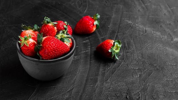 Erdbeeren in der schüssel auf schwarzer tabelle