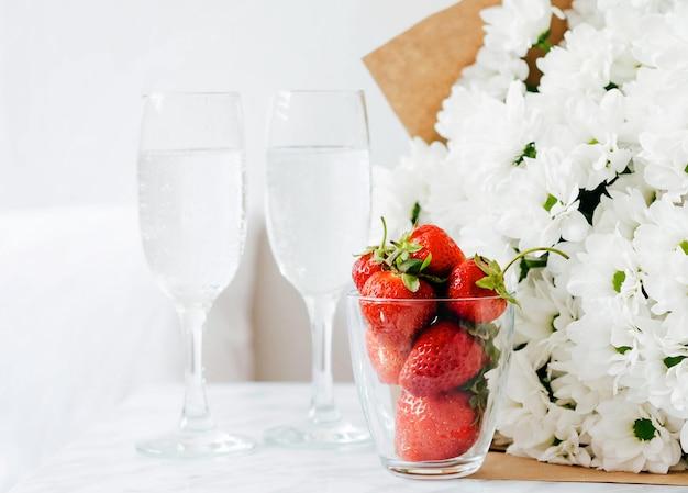 Erdbeeren in einem glas stehen vor dem hintergrund der gläser mit wasser und einem blumenstrauß