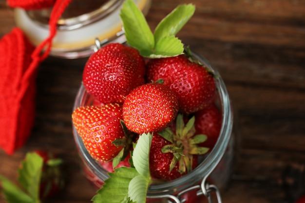 Erdbeeren in einem glas und in einer alten hölzernen retro- weinlese