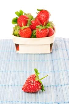 Erdbeeren in einem korb. an einer weißen wand.