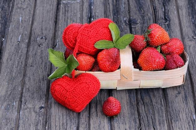 Erdbeeren in einem korb auf einem alten schäbigen hölzernen hintergrund rustikalen retrostil