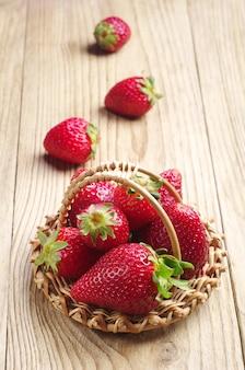 Erdbeeren in einem weidenkorb auf einem holztisch