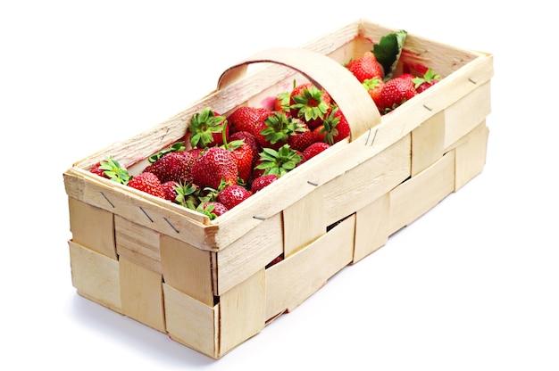 Erdbeeren in einem weidenkorb auf einem weißen hintergrund