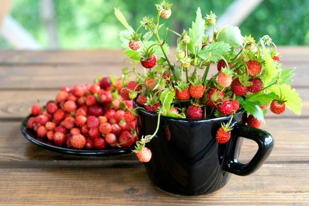 Erdbeeren in einem weißen becher auf einem rustikalen holztisch. das konzept von bio-lebensmitteln. rustikaler stil