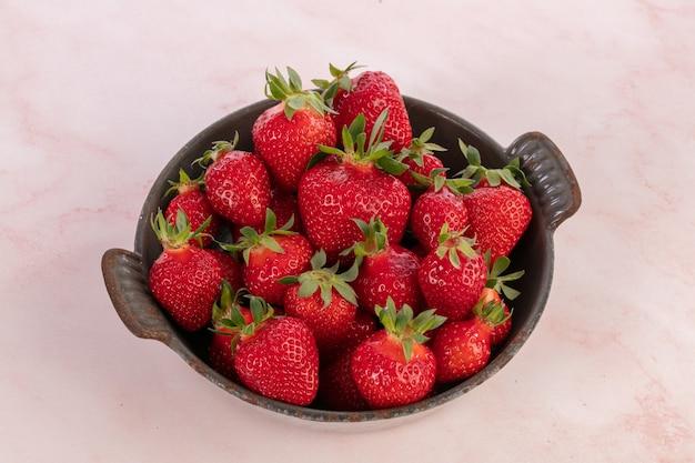 Erdbeeren in einer alten grau emaillierten schale auf rosa