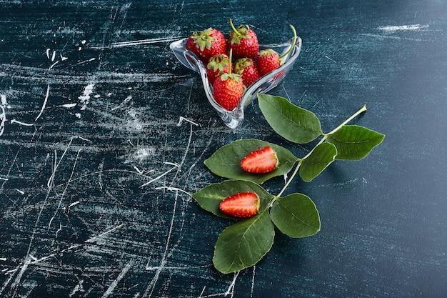Erdbeeren in einer dekorativen glasschale.