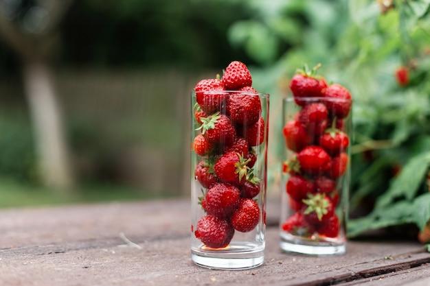 Erdbeeren in einer glasschale auf einem vintage-holztisch im garten in der nähe des busches
