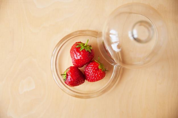 Erdbeeren in einer glasschüssel auf hölzernem hintergrund