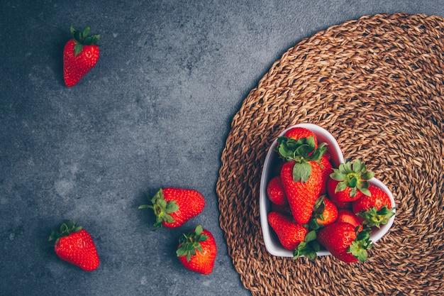 Erdbeeren in einer herzförmigen schüssel auf einem untersetzer und grauem strukturiertem hintergrund. draufsicht. freier speicherplatz für ihren text