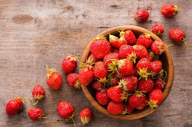 Erdbeeren in einer holzschale und herum auf einem holztisch. ansicht von oben