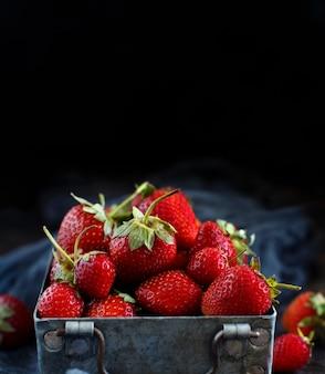 Erdbeeren in einer kiste auf einem dunklen holztisch