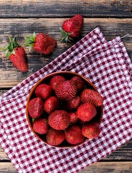 Erdbeeren in einer schüssel auf einem picknicktuch und einem holztisch. draufsicht.