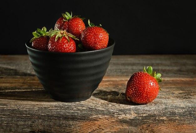 Erdbeeren in einer schüssel auf einer holzoberfläche. zurückhaltend.