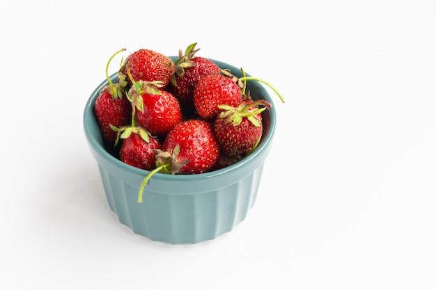 Erdbeeren in einer schüssel auf weißem hintergrund, horizontaler raum für text