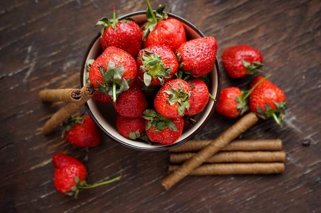 Erdbeeren in einer tonplatte mit süßen stäbchen schokoladenröhrchen