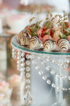 Erdbeeren in milchschokolade. erdbeeren auf einem mit kristallperlen verzierten glasständer. exquisite hochzeitsdessert. vegetarisches dessert.