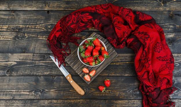 Erdbeeren in schüssel mit messer und rotem schal