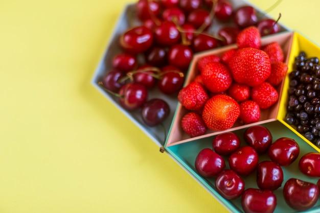 Erdbeeren, kirschen, blaue beeren auf bunter platte