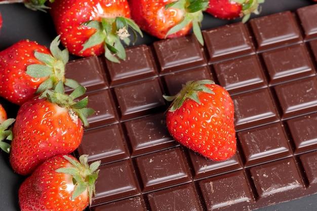 Erdbeeren mit einem dunklen schokoriegel