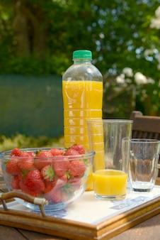 Erdbeeren mit einer flasche orangensaft auf dem tisch im garten