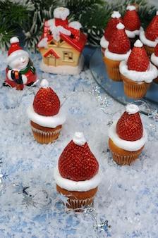 Erdbeeren mit schlagsahne in form einer weihnachtsmütze auf einem muffin