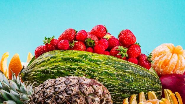 Erdbeeren; orangenfrucht; ananas und wassermelone auf blauem hintergrund