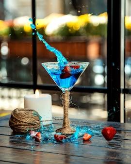 Erdbeeren spritzten in ein martini-glas blaue lagune