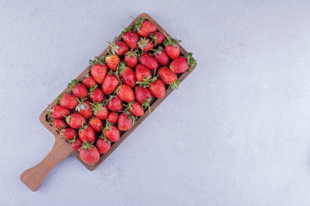 Erdbeeren stapelten sich in einem kleinen tablett auf marmorhintergrund. foto in hoher qualität