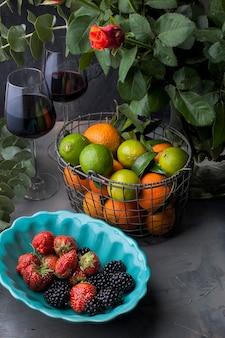 Erdbeeren und brombeeren in einer grünen platte und mandarinen in einem korb nahe einem vase mit einem rosenblumenstrauß, auf einem schwarzen hintergrund. zwei gläser rotwein