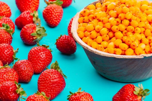 Erdbeeren und reife sanddornbeeren auf türkishintergrund