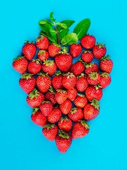 Erdbeeren und tadellose blätter auf blauem hintergrund