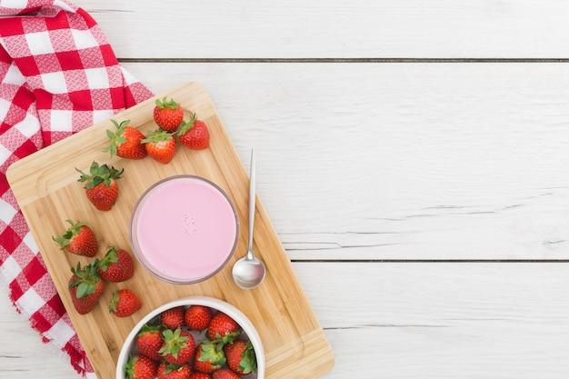 Erdbeeresmoothie auf hölzernem brett mit früchten