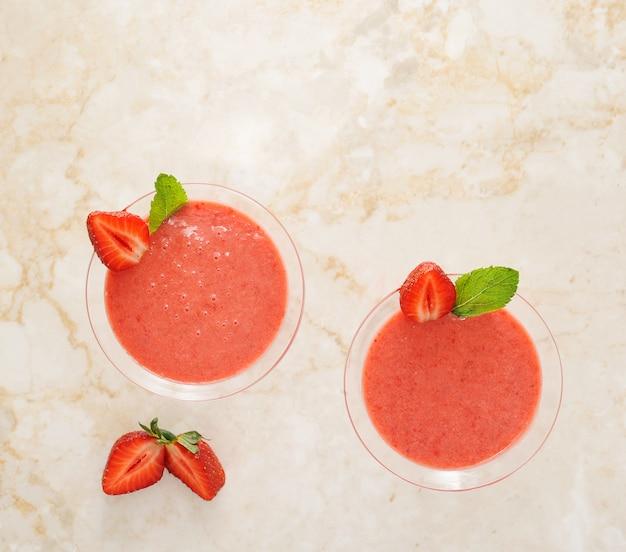 Erdbeeresmoothie im cocktailglas mit erdbeere und minze auf marmor
