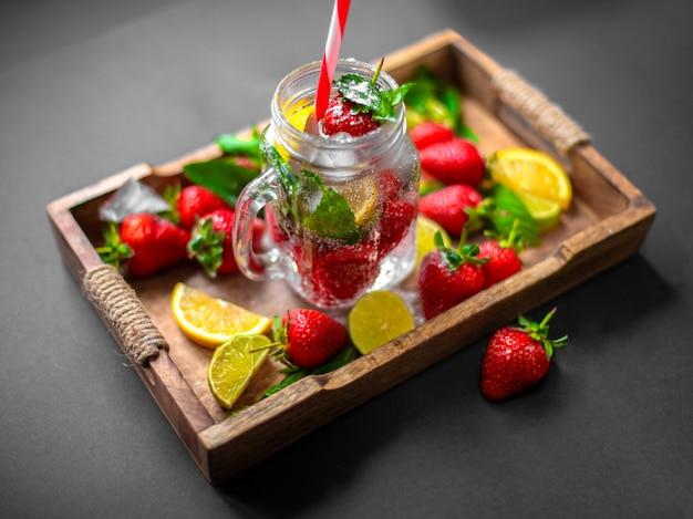 Erdbeerfrucht, tadellose blätter, kalk und zitronenhälften auf einem hölzernen behälter der weinlese.