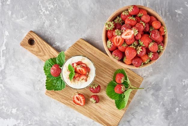 Erdbeergranola oder -smoothie in den glas- und frischen beeren in einer hölzernen schüssel, draufsicht. gesundes frühstück