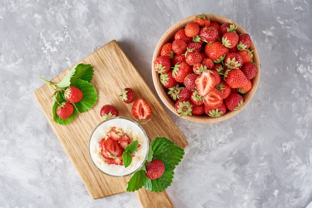 Erdbeergranola oder -smoothie in einem glas und in frischen beeren in der hölzernen schüssel, draufsicht, gesundes frühstück
