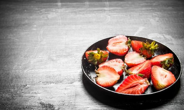 Erdbeerhälften in der alten platte. auf dem schwarzen holztisch.