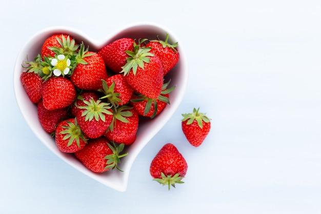 Erdbeerherz. frische erdbeeren im teller auf weißem holztisch. draufsicht, kopierraum.