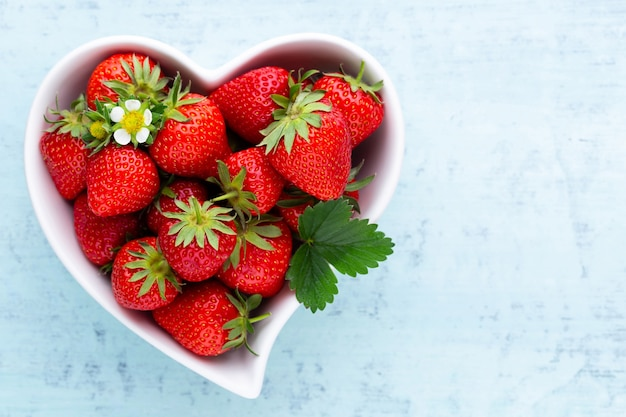 Erdbeerherz. frische erdbeeren im teller auf weißem holztisch.