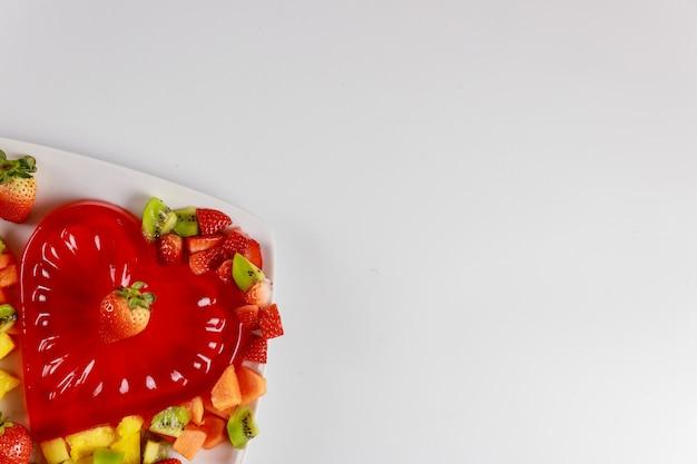 Erdbeerherzform gelatine mit früchten auf weißem teller