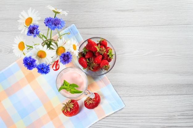 Erdbeerjoghurt in einem glas mit frischen erdbeeren, kamille, kornblumen auf einem holztisch mit serviette draufsicht